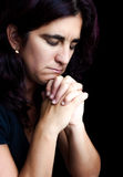 Hispanic woman praying isolated on black Stock Photo