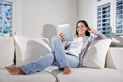 Hispanic woman reading electronic book on couch Royalty Free Stock Photos