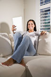 Hispanic woman reading electronic book on couch Royalty Free Stock Photo