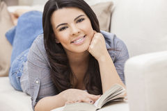 Hispanic Woman Reading Paperback Book at Home Royalty Free Stock Image