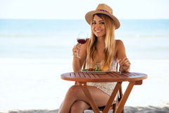 Hispanic woman relaxing at the beach alone. Beautiful Hispanic young woman enjoying a glass of wine and relaxing at the beach by herself royalty free stock photos