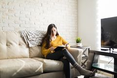Hispanic Woman Relaxing In Living Room. Young woman sitting on sofa while reading book at home stock photo