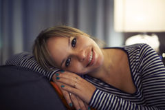 Hispanic woman relaxing on sofa and smiling Royalty Free Stock Photos