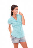 Hispanic woman in short jeans gesturing phone call Royalty Free Stock Image