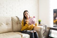 Portrait Of Woman Saving For Future. Hispanic woman showing large piggybank and representing savings concept royalty free stock images