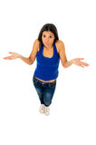 Hispanic woman shrinking shoulders open arms wondering confused in doubt. Young attractive hispanic woman in casual top and jeans shrinking shoulders open arms Royalty Free Stock Photography