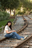 Hispanic woman sits on train tracks Stock Photo