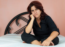 Hispanic woman sitting in her bed Royalty Free Stock Image