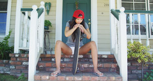 Hispanic woman sitting on porch with skateboard Stock Photo