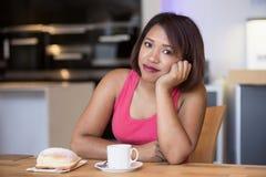 Hispanic woman sitting at table looking bored Stock Image