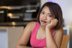 Hispanic woman sitting at table and looking sad Royalty Free Stock Photography