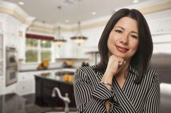 Hispanic Woman Standing in Beautiful Custom Kitchen. Attractive Hispanic Woman Standing in Beautiful Custom Kitchen Stock Images