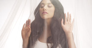 Hispanic woman standing behind curtain Royalty Free Stock Photos