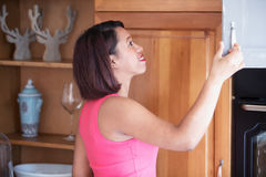 Hispanic woman standing in kitchen looking into cabinet Stock Photo