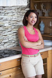 Hispanic woman standing in kitchen and smiles Royalty Free Stock Images