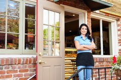 Hispanic Woman standing outside bakery. Smiling at camera Royalty Free Stock Photography
