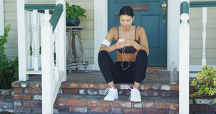 Hispanic woman starting playlist before going out for a run Royalty Free Stock Image