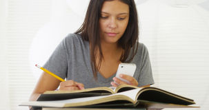 Hispanic woman studying and using smartphone on desk stock photos