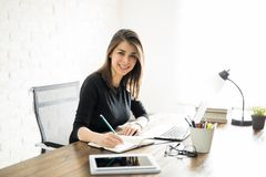 Hispanic woman taking some notes. Beautiful Latin woman working by herself in the office and taking some notes Royalty Free Stock Photos