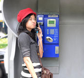 Hispanic woman talking in a public phone Royalty Free Stock Photo