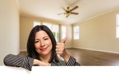 Hispanic Woman with Thumbs Up In Empty Room of House royalty free stock photography