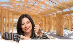 Hispanic Woman With Thumbs Up On Site Inside New Home Construction Framing. royalty free stock image