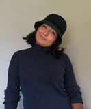 Hispanic woman tilting her head wearing a black wool cloche hat stock photography