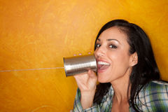 Hispanic woman with tin can telephone. Attractive Hispanic woman with tin can telephone Stock Photography