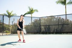 Hispanic woman training tennis on court. Strong young woman tennis player with balls and racket in hand practicing a serve on open court Stock Photography