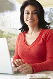 Hispanic Woman Using Laptop In Home Office Stock Photography