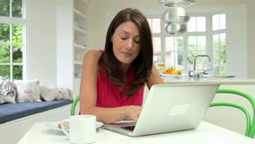Hispanic Woman Using Laptop In Kitchen At Home stock footage