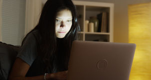 Hispanic woman using laptop at night Royalty Free Stock Photo