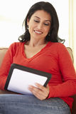 Hispanic Woman Using tablet computer At Home Royalty Free Stock Image