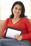 Hispanic Woman Using tablet computer At Home Stock Image