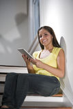 Hispanic woman using tablet computer on stairs Stock Image