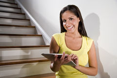 Hispanic woman using tablet computer on stairs Royalty Free Stock Images