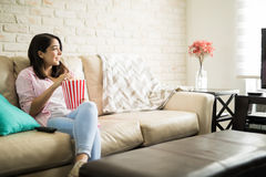 Hispanic woman watching movies by herself Stock Photos
