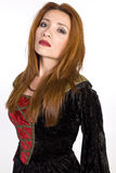 Hispanic woman wearing a costume dress. A red headed Hispanic woman wearing a costume style velvet dress and staring with a serious look toward the camera Royalty Free Stock Image