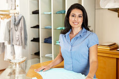 Hispanic woman working in fashion store. Smiling and standing at camera Stock Photo