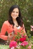 Hispanic Woman Working In Garden Tidying Pots Royalty Free Stock Photos