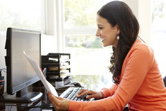 Hispanic woman working in home office Stock Photo