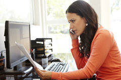 Hispanic woman working in home office stock photos