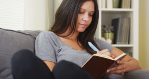 Hispanic woman writing in her diary Stock Image