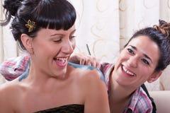 Hispanic women having fun while body painting stock images