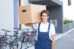 Hispanic worker with box in front of a building Stock Photos