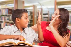 Hispanic Young Boy and Female Adult High Five Studying. Hispanic Young Boy and Female Adult High Five While Studying At Library royalty free stock image