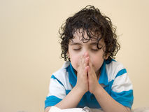 Hispanic Young Child Praying. Young Latin boy praying. Praise, faith and reverence in a kid. Daily devotional of a religious child with curly hair Stock Photo