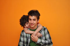 Hispanic Young Boy Showing Love to Older Brother royalty free stock image