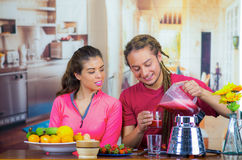 Hispanic young healthy couple enjoying breakfast together, sharing fruits, drinking smoothie and smiling, home kitchen. Background Royalty Free Stock Photo
