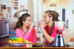 Hispanic young healthy couple enjoying breakfast together, sharing fruits, drinking smoothie and smiling, home kitchen. Background Royalty Free Stock Images